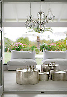 Round, metal tables from Morocco add a new dimension to the white flooring and furnishings on the terrace