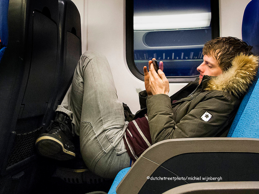 Nederland, Amsterdam, 2 april 2013<br /> Jongen hangt in de trein terwijl hij met zijn smartphone bezig is.<br /> Foto(c): Michiel Wijnbergh