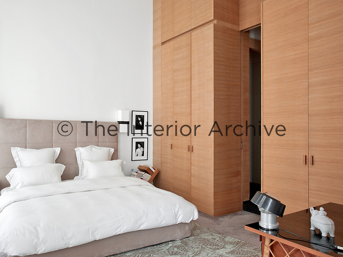 Floor-to-ceiling bespoke wardrobes provide ample storage in the master bedroom