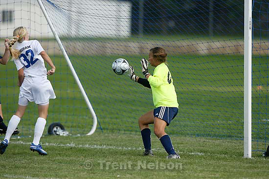 South Jordan - Bingham's Randy Sorensen knocks the ball in for a goal against Juan Diego goalkeeper Allison Bruder. Bingham vs. Juan Diego girls high school soccer Tuesday, August 25 2009. 3A Juan Diego managed to tie 5A Bingham 3-3..