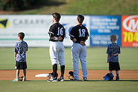 Grant Massey (16) and Bradley Strong (18) of the Kannapolis Intimidators are joined on the field by two youth baseball players prior to the game against the Augusta GreenJackets at Intimidators Stadium on May 30, 2016 in Kannapolis, North Carolina.  The GreenJackets defeated the Intimidators 5-3.  (Brian Westerholt/Four Seam Images)