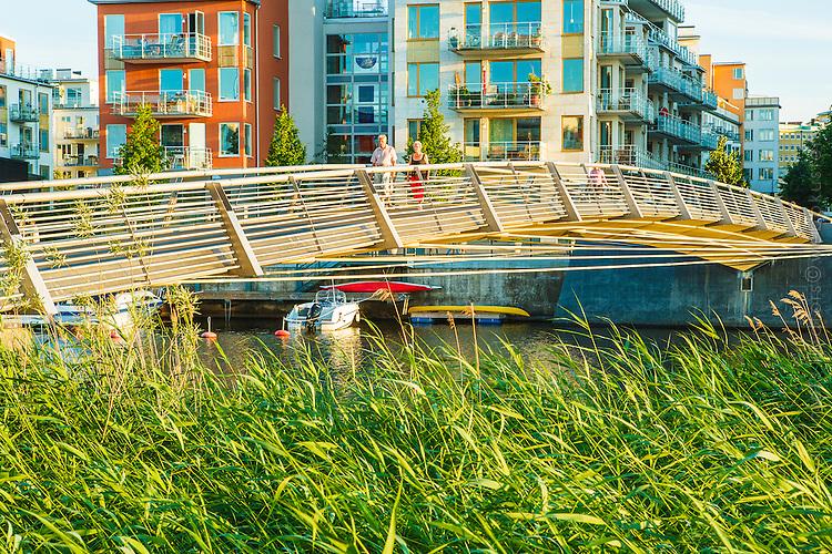 Bro över kanal med promenerande par i Hammarby sjöstad Stockholm