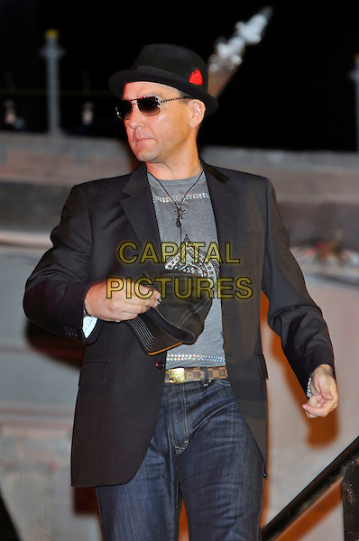 VINNIE JONES.Leaving The Big Brother House, Celebrity Big Brother Final 2010, Borehamwood, Hertfordshire, UK.29th January 2010.final BB CBB half length black hat sunglasses grey gray t-shirt jeans hand holding baseball cap  jacket blazer .CAP/PL.©Phil Loftus/Capital Pictures.