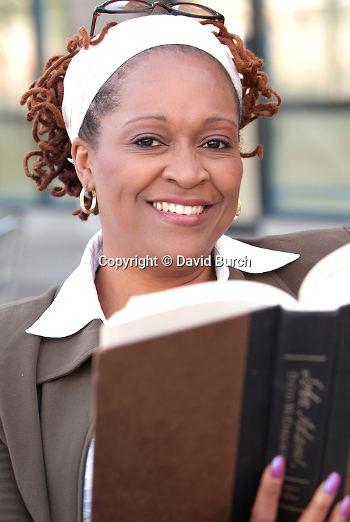 African American woman reading a book, smiling
