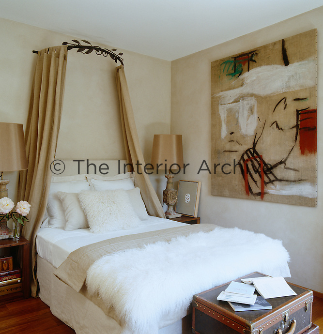 In a girl's bedroom the bed is crowned by an antique corona and draped with linen panels