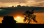 Old farm house silhouette at sunset