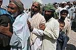 Men and boys line up for free medical assistance, food parcels and winter clothes outside a police headquarters in Kandahar, Afghanistan. U.S. forces distributed aid to several hundred people before the event was shut down after the crowd grew unruly and supplies began to run low. Aug. 18, 2008. DREW BROWN/STARS AND STRIPES