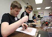 NWA Democrat-Gazette/DAVID GOTTSCHALK  Justus Lynch (left), 13, works with Camdyn Olszewski, 9, Monday, March 19, 2018 in the Nerdies Spring Break Session Build a Modbot Robot at the NWA Fab Lab in Fayetteville. The three day camp for students ages 9-15 is a partnership between the New Design School and NWA Fab Lab. The students will build, wire, program and then bring the modbot robots home. The students also learned the essentials of soldering and Arduino Programming.