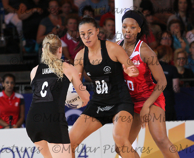 Laura Langman passing to Maria Tutaia watched by Eboni Beckford-Chambers in the Team New Zealand against Team England in the Netball Semi Final for the 20th Commonwealth Games, Glasgow 2014 at the Scottish Exhibition and Conference Centre, Glasgow on 2.8.14.