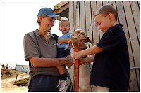 A grandmother inspects a goat at a farm with her grandsons. Model released image can be used to illustrate many purposes.
