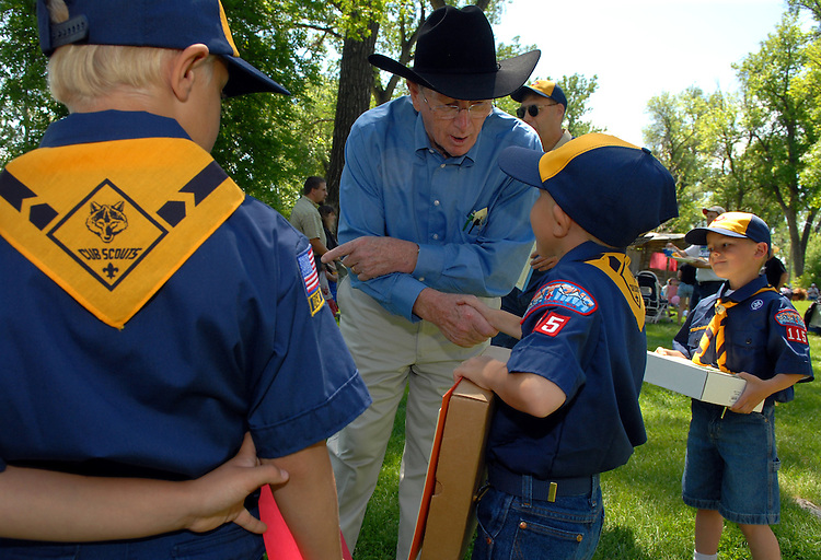 Sen. Conrad Burns, R-Mont., hands out American Flags to Cub Scouts from Terry Mont., after the Bucking Horse Sale parade in Miles City, Montana.