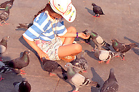 Girl age 12 feeding pigeons in city center.  Krakow Poland