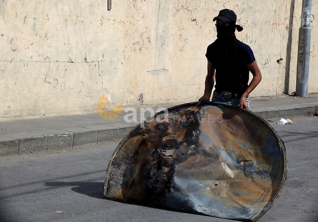 A Palestinian protester takes cover during clashes with Israeli police in Jabal al-Mukaber neighborhood, southern Jerusalem, on October 13, 2015. A wave of stabbings that hit Israel, Jerusalem and the West Bank this month along with violent protests in annexed east Jerusalem and the occupied West Bank, has led to warnings that a full-scale Palestinian uprising, or third intifada, could erupt. The unrest has also spread to the Gaza Strip, with clashes along the border in recent days leaving nine Palestinians dead from Israeli fire. Photo by Mahfouz Abu Turk