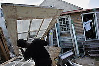 New Orleans, La.- Lower 9th Ward residents are rebuilding their historic neighborhoods slowly. Longtime Holy Cross neighborhood resident Keith Calhoun,right, watches as his son Keith Calhoun Jr. delivers salvaged doors as they work to rebuild a home he recently purchased, August 17,2007. Calhoun's home, a few doors down, was completed destroyed during Hurricane Katrina.