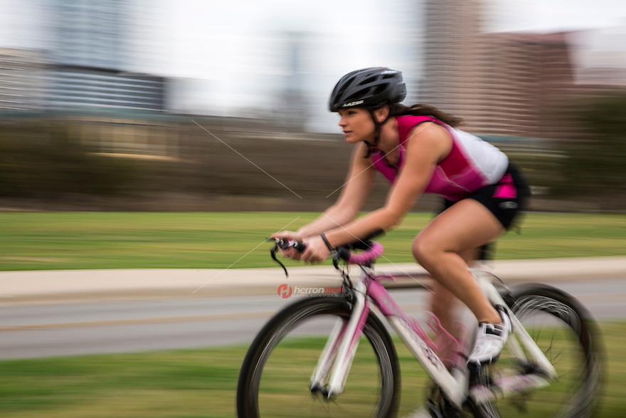 An attractive fit young woman athlete  rides a high-end bike/cycle training for triathlon on Lady Bird Lake Trail in downtown Austin, Texas