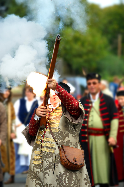 Man firing a musket in tradtional Hungarian costume celebrating the wine festival - Badascony, Hungary