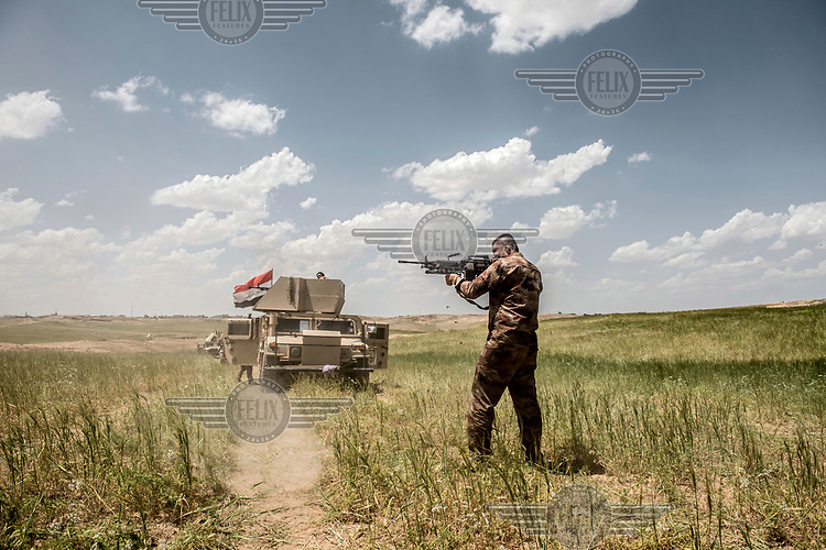 An officer with the Iraqi army's 16th Division fires at ISIS positions in some buildings a few hundred metres away, at the start of a new offensive on the north western edge of Mosul.
