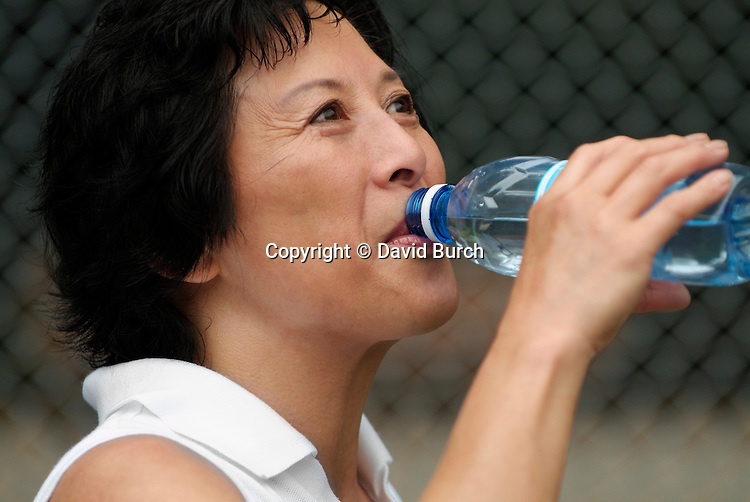 Asian woman drinking bottled water after tennis game