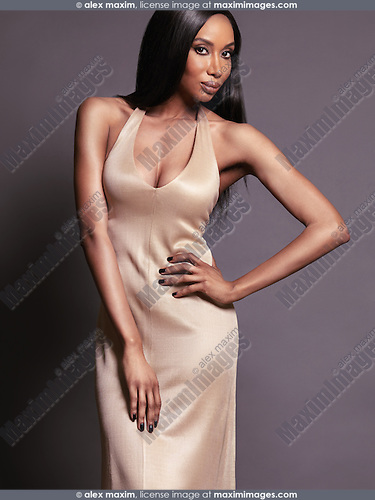 Fashion portrait of a beautiful african american woman wearing a gold dress. Isolated on gray studio background.