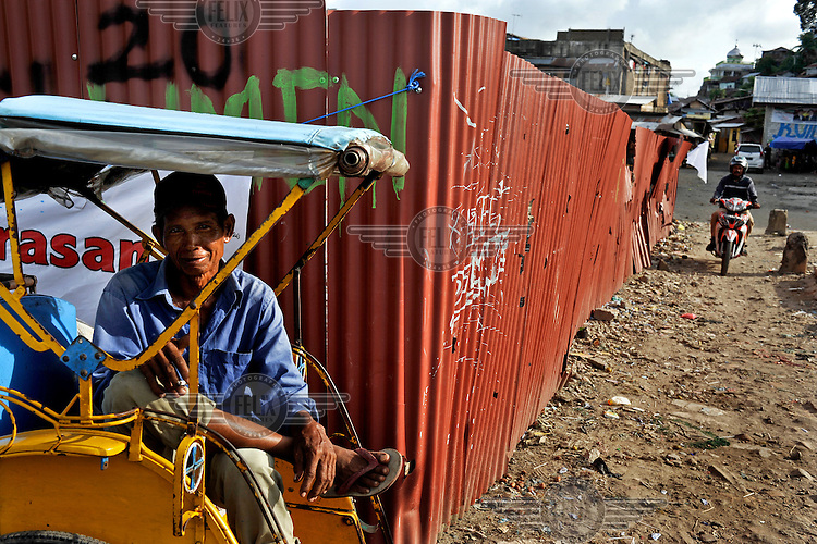 A becak pedicab rider waits for a fare in an area of cleared land demarcating the approximate dividing line between Christian and Muslim areas in central Ambon City. The 1999-2002 religious war between Maluku's Christian and Muslim populations, mainly centred on Ambon Island, led to over 5000 deaths and to around 500,000 people become displaced. Destroyed homes and offices, churches and mosques are slowly being either torn-down or renovated.  Urban centres, such as Ambon City, continue to be split along largely sectarian lines, and tensions are never far below the surface. Riots between Christian and Muslim youths erupted in September 2011 and, most recently, June 2012, though luckily simmered down just as quickly, partly due to community leaders learning how to defuse tensions from the earlier, more devastating, conflagration. /Felix Features