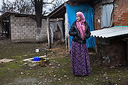 Aset Borchashvili, 43, poses in the yard from where her son was abducted by security forces. Unlike many others before, she is aware of his whereabouts. Her son, Yusup Ektumayev, is accused of participating in a terror attack and is awaiting trial in a detention centre. Mrs. Borchashvili claims that he was forced to confess under torture. Assinovskaya, Chechnya, Russia, 2013