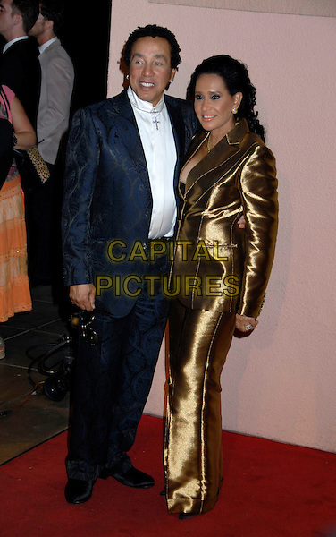 SMOKEY ROBINSON & GUEST.The 2007 Sony / BMG Grammy After Party held at the Beverly Hilton Hotel, Beverly Hills, California, USA. .February 11th, 2007.full length black suit gold dress .CAP/ADM/GB.©Gary Boas/AdMedia/Capital Pictures