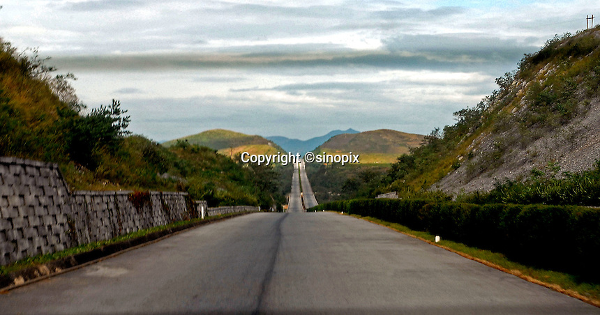 "A deserted road in North Korea. The DPRK (Democratic People's Republic of Korea) is the last great dictatorship where the people are bombarded with images of the ""Eternal President"" Kim Il-sung who died in 1994 and his son and current leader Kim Jong-il who are worshipped like a God."