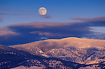 The full moon over snow covered trees on the hills above Missoula, Montana