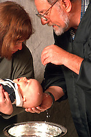 Minister baptizing baby boy held by grandmother ages 60 and 55.  St Paul Minnesota USA