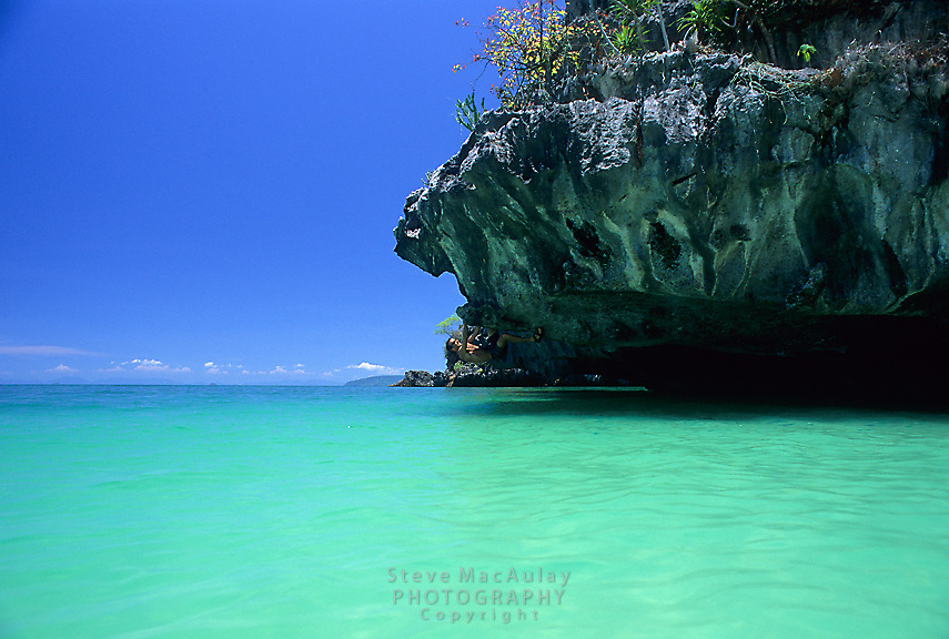 Male traveler climbing overhang about stunning green turquoise water, Phra Nang Beach,Railay Rei Lei, Thailand