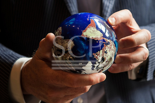 London, England. A businessman in a suit holds, turns a colourful globe in his hands. The world spins.