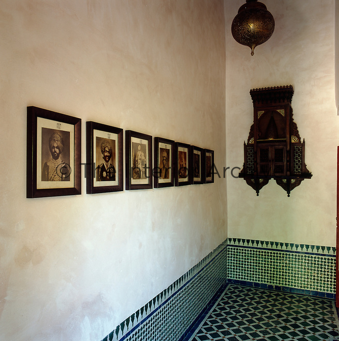 The lower area of the walls are lined with decorative green and white tiles. Portraits of Sikhs and a carved wall shrine decorate the walls
