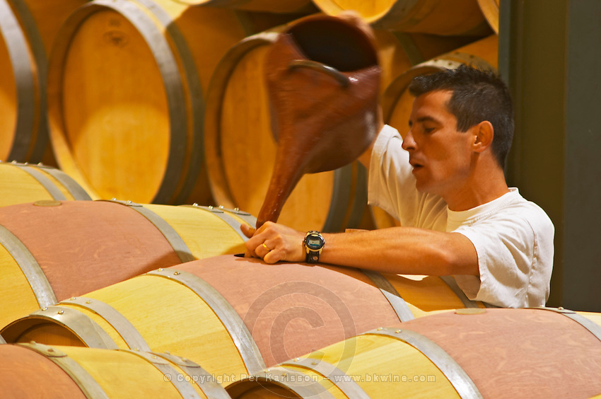The barrel aging cellar with a man topping up wine (ouillage) in barrels with what looks like a garden watering can. Note that the man keeps his finger in the bung hole to check when the barrel is filled up. Chateau Paloumey Haut-Medoc Ludon Medoc Bordeaux Gironde Aquitaine France
