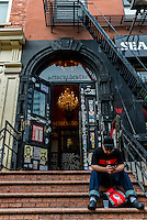 New York, NY 6 November 2015 - Man texting on an iPhone sitting on the stoop of a shop named Search & Destroy on Saint Mark's Place