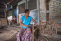 Myanmar/Burma, Yangon. Htauk Kyant region. Daw Myint Kyi runs a small business making bamboo baskets. Her husband died so she is the main income earner for her two sons. She has 11 brothers and sisters & with two of her sisters they took over the bamboo business from her father. They make about 25 pieces in one day, fulfilling orders and get paid per basket so she works every day and they make about $420 a week. She wants to buy more bamboo with her BRAC loan.