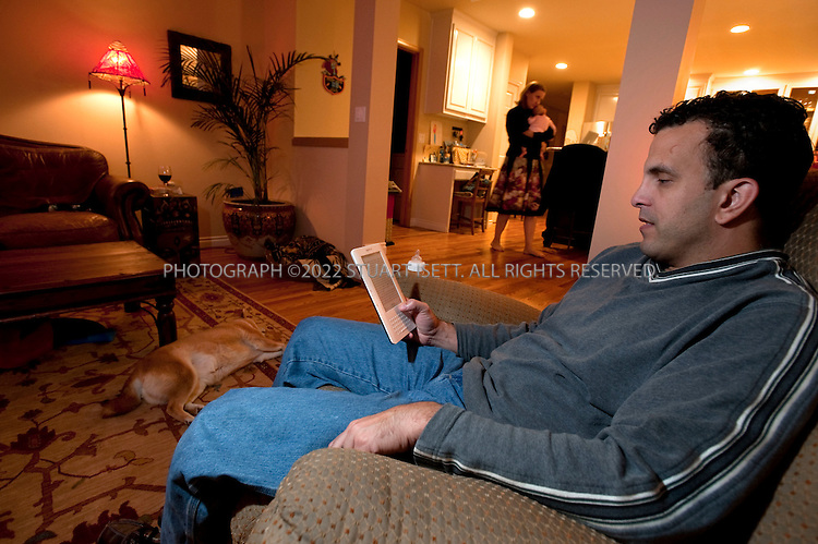 10/13/2009--Woodinville, WA, USA..Brandon Watson at home reading his Amazon Kindle. Mr. Watson went from reading one book a month to several since he got his Kindle...©2009 Stuart Isett. All rights reserved.