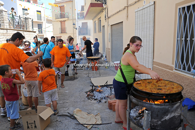 "Groups of friends or ""penyas"" make large paellas in the square surrounding the church for the lunch hour during the municipal fiestas in Costur, Spain on August 15, 2009."
