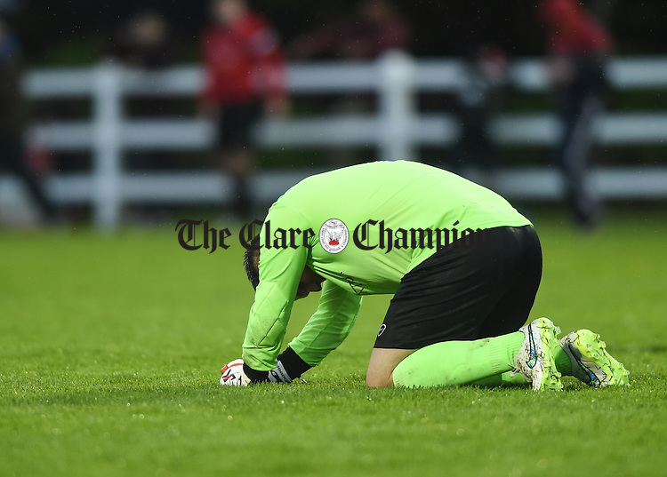 A disappointed John Mulready of Bridge United at the final whistle as  Newmarket Celtic celebrate their win over  Bridge United during their Cup final at Doora. Photograph by John Kelly.