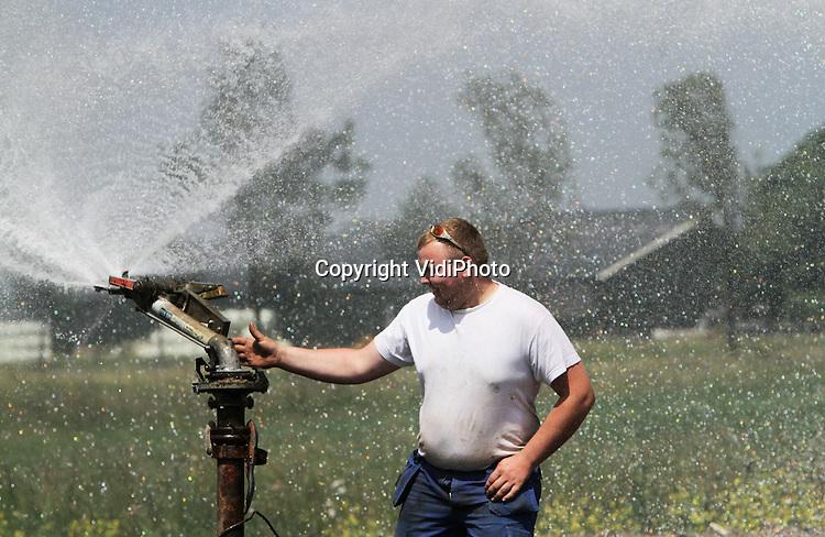 """Foto: VidiPhoto..VALBURG - Worstelen met een nieuw tweedehands waterkanon. Personeel van veehouder Erik Timmermans uit Valburg probeert vrijdag een waterkanon in de juiste stand te krijgen. Op de 8 ha. grote akker van Timmermans moet met spoed maïs ingezaaid worden en daarvoor is vooraf zo'n 20 mm water nodig. De installatie doet daar twee dagen over. Nog niet eerder heeft Timmermans de maïs zo laat ingezaaid. Omdat het veevoer peperduur is, rest hem geen andere mogelijkheid dan zelf maïs verbouwen. Op een eerder ingezaaide akker is het """"vechten tegen de droogte"""" en groeit de maïs nauwelijks. De Valburgse veehouder bezit 80 melkkoeien en 500 melkgeiten.."""