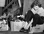 Mary Ann Alisaukus of North Riverside Street, Waterbury's most stricken street, tries on a pair of shoes.