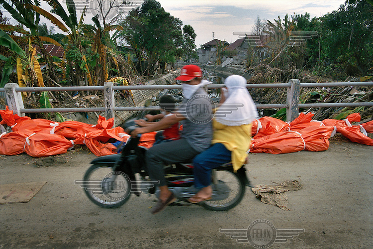 A family on a motorbike pass body bags lining a quiet lane in the Pugee district, following the tsunami which struck South Asia on 26/12/2004..An underwater earthquake measuring 9 on the Richter scale triggered a series of tidal waves which caused devastation when they struck dry land. 12 countries were affected by the tsunami, with a combined death toll of over 280,000. Aceh, the closest landfall to the epicentre of the quake, suffered the greatest loss of life.