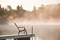 Morning mist Adirondack chair and dock along the Michigamme River at Republic Island Cottage near Republic Michigan.