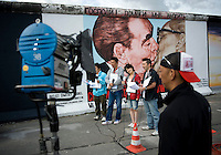 A Japanese TV team at the East Side Gallery in front of the famous Berlin Wall painting of Soviet leader Leonid Brezhnev kissing East German leader Erich Honecker. First painted in 1990, the Russian artist Dmitry Vrubel is restoring his painting, after two decades of weathering and graffiti, for the 20th anniversary of the fall of the Berlin Wall in November 2009..