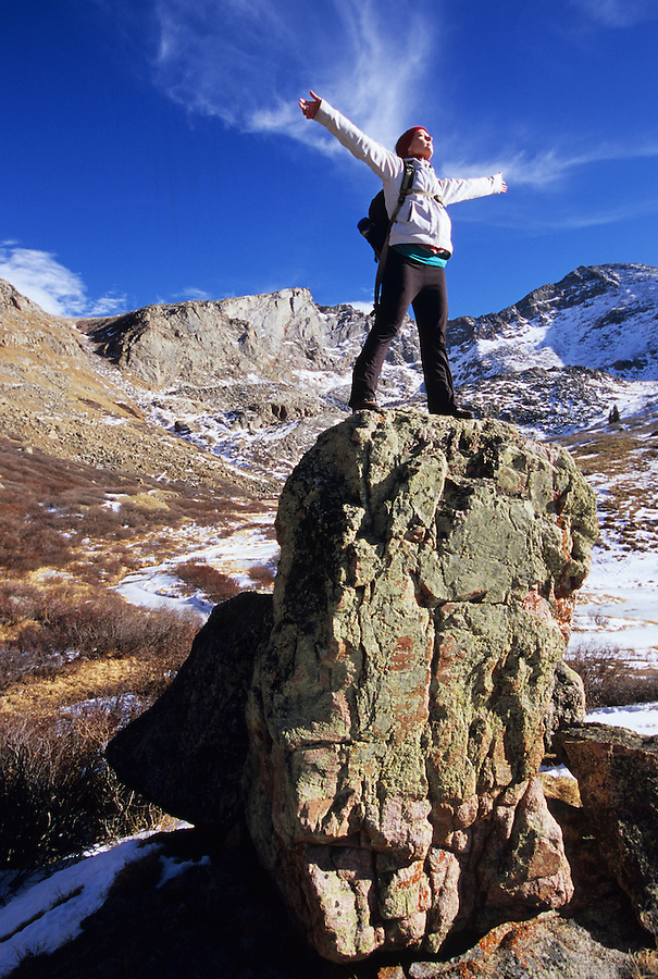 Feeling the warm winter sun against her skin, this climber seeks higher ground to spread her wings, near The Sawtooth and Mt. Bierstadt, Colorado.