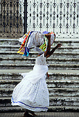Salvador, Bahia, Brazil. Bahiana woman carrying a basket of scarves on her head outside the church of Nosso Senhor do Bonfim.