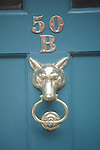 A light blue door with a gold knocker in the shape of a fox head on a house in Beacon Hill in Boston, MA.