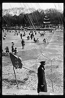 Chinese enjoy ice skating on a frozen lake as a security guard looks on during weekend in Beijing, China in February 2011. (Leica M6, 50mm f2, Kodak Tri-X film)
