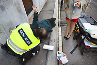 Switzerland. Canton Ticino. Lugano. Day scene for a medical emergency intervention. An elderly man fell on the ground and has hurt himself badly. A sexy woman with beautiful legs, a red mini skirt and high-heeled shoes stands-by and holds in her hands a bottle of water. The aged man needs to be brought by ambulance to hospital for a medical examination. He holds his arm up. A paramedic wears  a blue uniform and works for the Croce Verde Lugano. He is a professional certified nurse. The Croce Verde Lugano is a private organization which ensure health safety by addressing different emergencies services and rescue services. 28.01.2018 © 2018 Didier Ruef