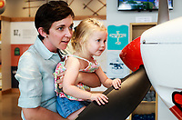 NWA Democrat-Gazette/CHARLIE KAIJO Rebekah Kingsley of Bentonville holds up Anna Grace Kingsley, 3 so she can see the engine of an XA42 airplane, Friday, July 6, 2018 at the OZ1 Flying Club pop-up shop in Bentonville. <br />