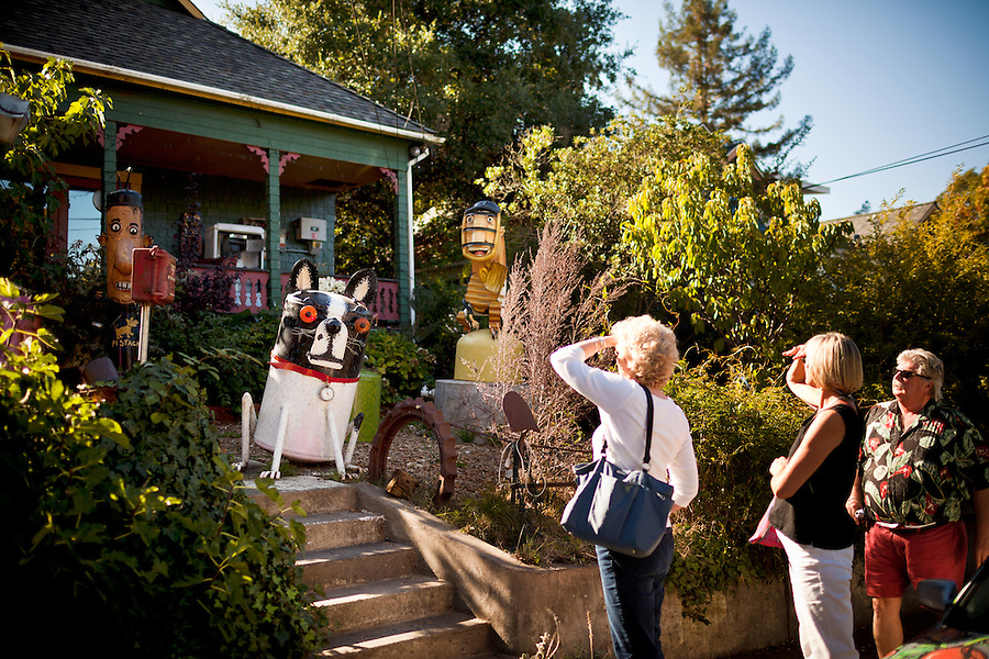 Bren Betcone, of San Francisco, with her husband, Jim Klein, far right,  and friend Tineke Lanser (CQ), of nearby Forestville, stroll past the  home of artist Patrick Amiot who installed his metal sculptures in his front yard, and his neighbors gardens along Florence Ave, in Sebastopol, Ca., on Saturday, Oct. 9, 2011. In recent years, new restaurants, shops and live music venues have opened in Sebastopol, securing the town as an arts and culture hub.